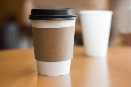 Dos tazas de café de papel sobre la mesa de madera