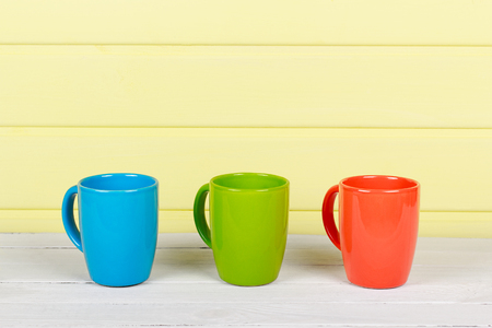 cupping glass cupping: Three Colorful Cups on Wood Table as background Stock Photo