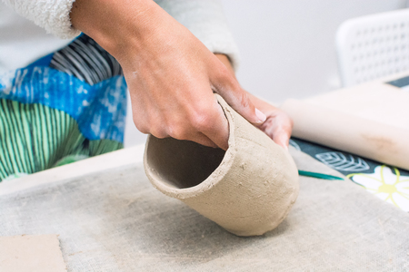 proffesional occupation: Woman working with raw clay in workshop. Human hands making clay cup.