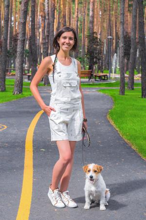 여자는 흰색 강아지와 함께 공원에서 포즈