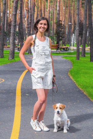 Woman posing in a park with white dog