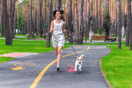 행복 한 미소 짓는 여자와 그녀의 강아지는 녹색 여름 공원에서 실행합니다. 애완 동물 및 인간의 스포츠 활동 민첩성