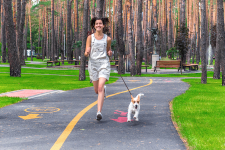 Happy smiling woman and her dog running in a green summer park. Pet and human sports activity agility