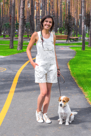 White dog and young woman posing in a park at summertime