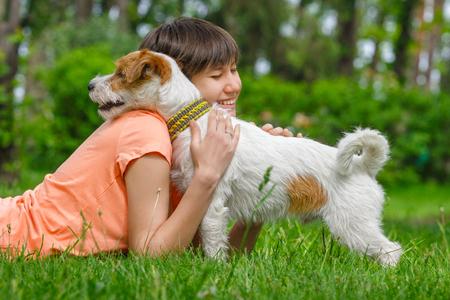 젊은 여자와 개가 껴안고 및 함께 야외에서 재미 녹색 잔디 누워