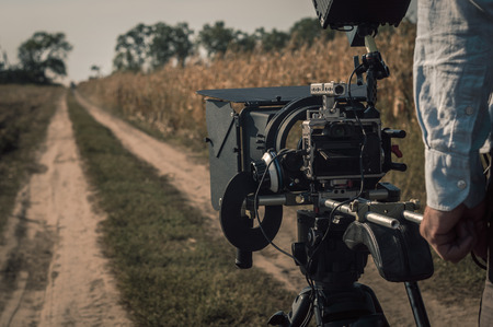 Operator filming with compact mirrorless camera rig outdoors. Filmmaking scene 版權商用圖片