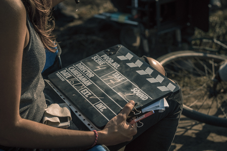Woman holding clapperboard