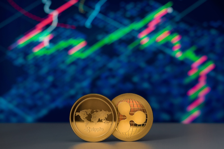 Ripple Cryptocurrency coins over financial charts on background