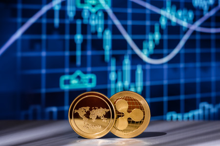 Two golden Ripple XRP crypto coins with Cryptocurrency Financial Charts and Graphs