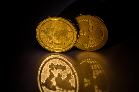 Shiny Golden XRP cryptocurrency coins on dark background with reflection