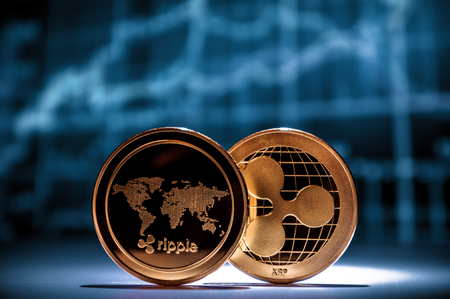 Two golden xrp ripple coins with financial charts on background. Cryptocurrency business con 版權商用圖片