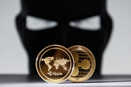 Ripple golden coins with a robber hacker wearing face mask. Cryptocurrency financial criminal concept