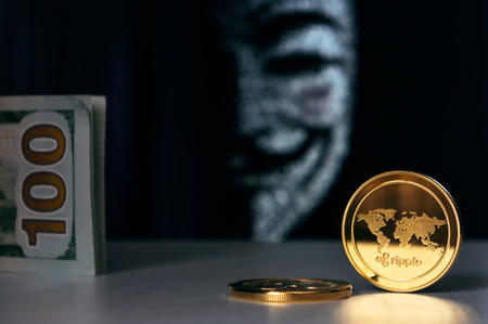 Ripple coins and american dollars with anonymous face mask on background. Cryptocurrency security concept.