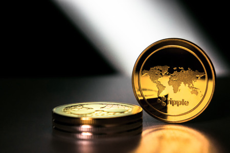 XRP golden coins on dark background. Ripple is a real-time gross settlement system, currency exchange and remittance network