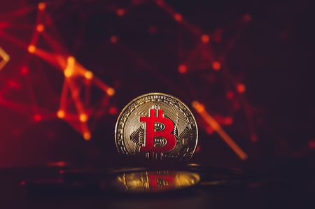Bitcoin cryptocurrency coin on dark red background