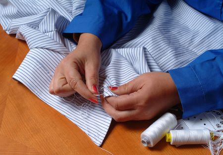 Close up of tailors hands sewing on businessman clothes