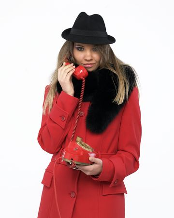 Young woman on an old red phone photo