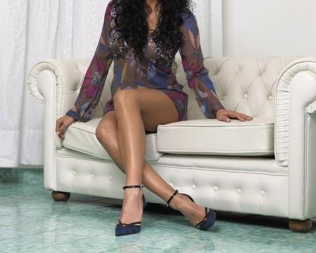 crossing legs: womans legs on sofa Stock Photo