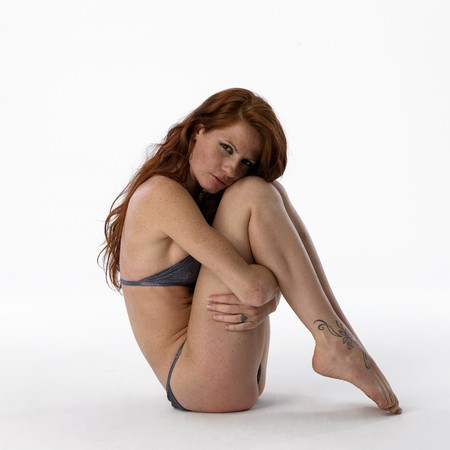 parte: Young woman in bikini crouched on a white background