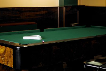 billiards room: A billiards table without balls in a games room