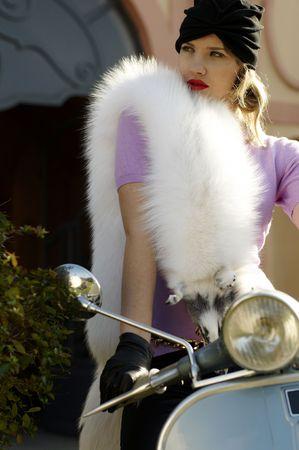 Beautiful elegant woman posing on a scooter photo