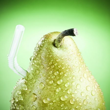 Green pear with straw, like a fruit juice ! Stock Photo