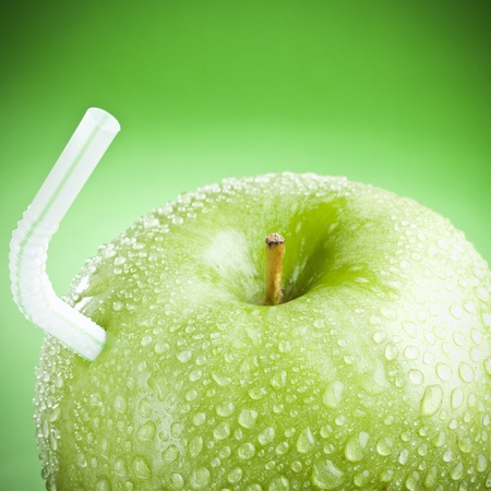 Green apple with straw, like a fruit juice ! Stock Photo