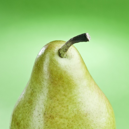 Tasty ripe green pear isolated on a green background Stock Photo