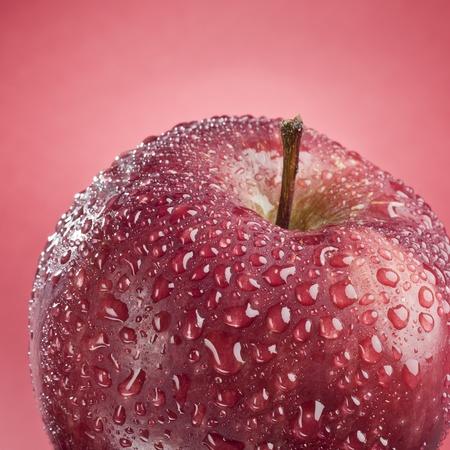 Tasty ripe red apple isolated on a red background Stock Photo