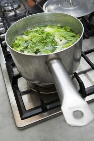 escarole: Cooking the escarole in a kitchen for a good vegetarian recipe  Stock Photo