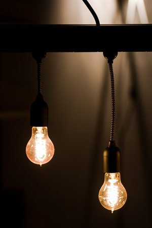 Bulbs hanging from a current thread in a dark room , creates a magical atmosphere Stock Photo