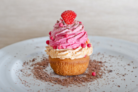 a sweet cupcake with chocolate shavings for your breakfast or as dessert for the evening , on a white ceramic plate