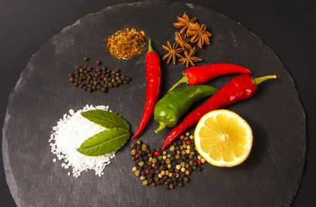 anis: Exposition close up of fresh organic peppers, half of lemon, mont leave, salt and anis on dark background. Healthy cocking, stone cutting board, chili pepper, red and green pepper.