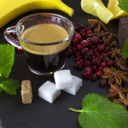 Exposition close up of fresh organic fruit and chocolate with coffee cup, chili pepper, half of lemon, sliced ??��banana, mint leaf, cinamone, blackberry and coffee grape on black background, rock board