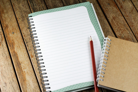 note pad: notepad and pencil on a wood desk, add your text here.