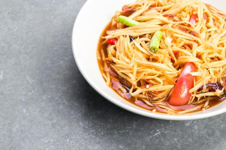pu dong: papaya salad (Som-tam) in dish on table
