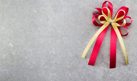 your text: Red and gold bow of ribbon on cement background for fill text in space