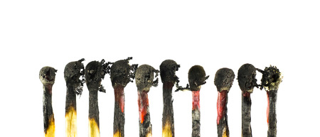 Matches burned into charcoal on white isolate background. Stock Photo