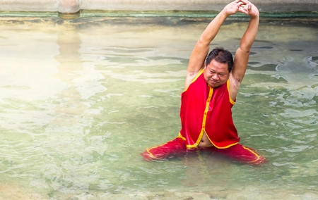 Thailand, Samutprakan,June 11, 2017: Actor is Warm up body before the crocodile Show. Warm up in crocodile pond to keep the body wet and smell like a crocodile. At Samut Prakan Crocodile Farm and Zoo.