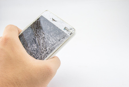 Mans hand holds mobile phone with broken touchscreen on white background. Zdjęcie Seryjne