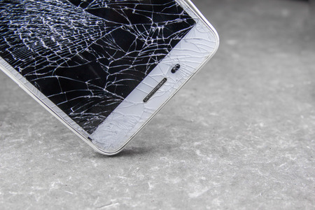 Mobile phone with broken touchscreen on gray background. Zdjęcie Seryjne