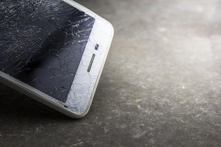 Mobile phone with broken touchscreen on gray background. 写真素材