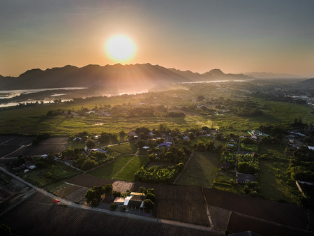 Aerial photo of rice fields, mountains, houses of rural villages in Thailand. 写真素材