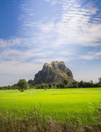 Small mountain is majestically surrounded green fields in Thailand. 写真素材