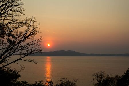 Landscape of The sunshine at dusk with the beachside trees that reflect the sea and Koh Samet of Thailand. 写真素材