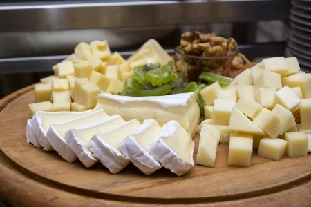 antipasto: Assorted cheese and dried fruits on a wooden board Stock Photo