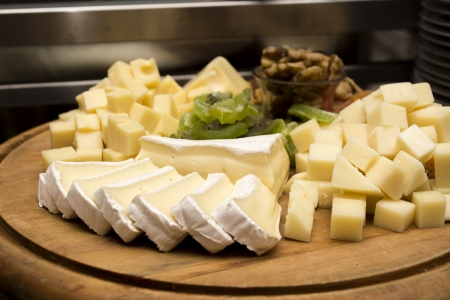 Assorted cheeseon a wooden board under dim light photo