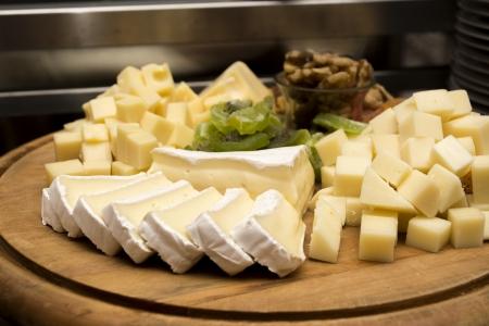dim light: Assorted cheeseon a wooden board under dim light Stock Photo
