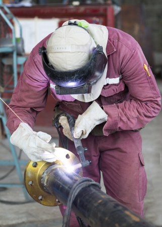 Craftsman in a safety suit is welding a metal pipe photo