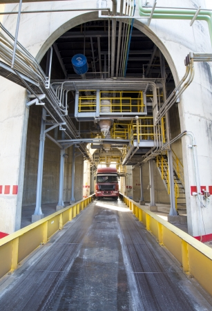 Truck loading a product under factory silo photo